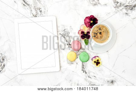 Tablet PC coffee french cookies macaroons pansy flowers. Floral flat lay with space for your text or picture