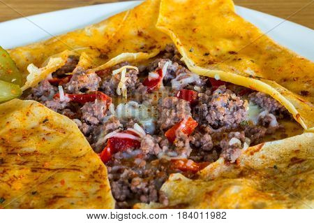 Closeup Of A Delicious Crepe With Ground Meat Served On A White Plate