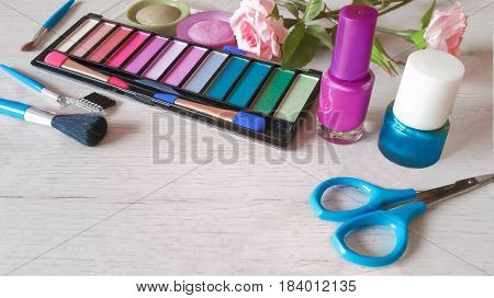 Colorful set of cosmetics and nail polishes on white wooden background