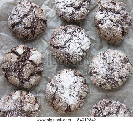 Chocolate crackle cookies with powdered sugar coating.