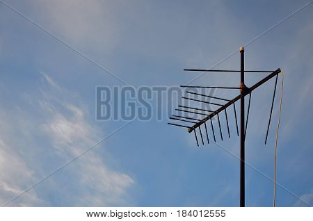 An Old And Rusty Television Antenna Against A Cloudy Blue Sky