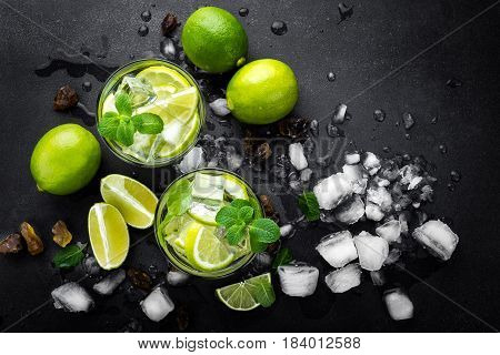 Refreshing mint cocktail mojito with rum and lime cold drink or beverage with ice on black background top view