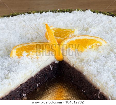 Closeup Of A Sliced Delicious Chocolate Cake With Coconuts And Orange Slices