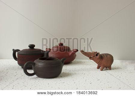 A funny clay elephant looks at three clay pots