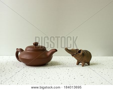 A funny clay elephant looks at the clay pot