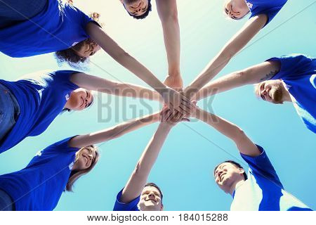 Team of volunteers putting their hands together as symbol of unity, bottom view