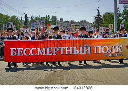 Volgograd Russia - May 09 2016: People hold banner of Immortal regiment and portraits of their relatives on Victory day in Volgograd