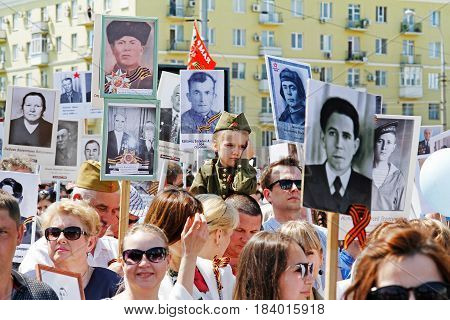 Volgograd Russia - May 09 2016: A girl in military uniform sits on shoulders of her father in the action