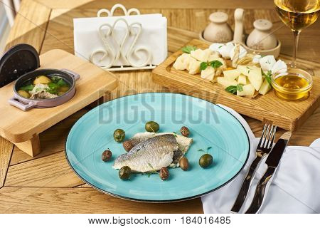 Dorada fillet with olives, cheeseplate, soup with meatballs and glass of white wine served on wooden table in restaurant