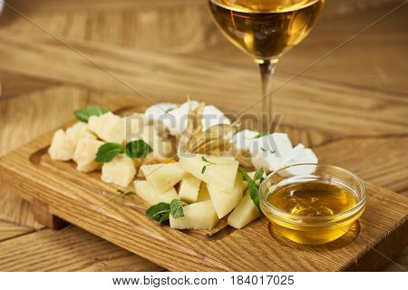 Cheese plate with mozarella, parmesan, honey and glass of white wine.