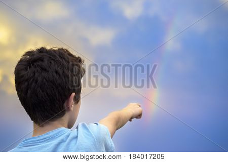 A young boy excitedly pointing at a rainbow in the sky in awe