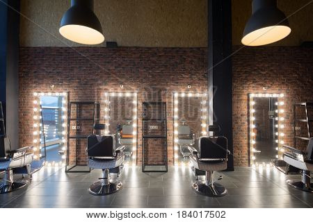 Empty barbershop with places for hairdresser and make-up artist work - seats and mirror with illumination