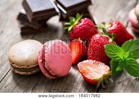 Macarons on a wooden plate with fresh strawberry fruits and chocolate