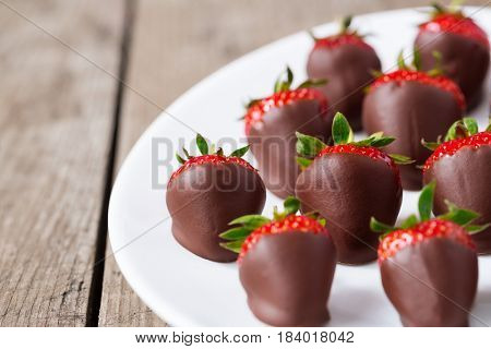Fresh strawberries dipped in chocolate sauce on plate
