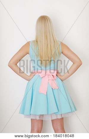 Young blonde in dress with bow poses near white wall in studio, back view