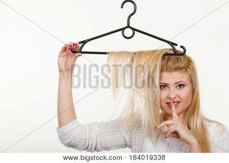 Wardrobe accessories haircare hair styling and selling concept. Blonde woman holding hair on clothes hanger