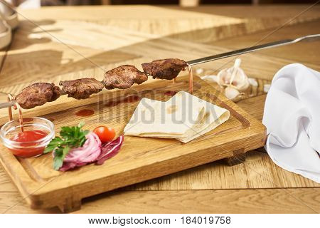 barbecue meat with fresh vegetables, ketchup sauce and bread on wooden board