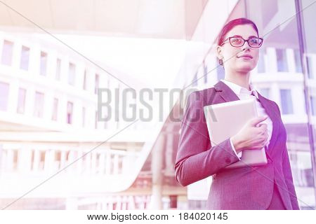 Confident businesswoman holding tablet PC outside office building