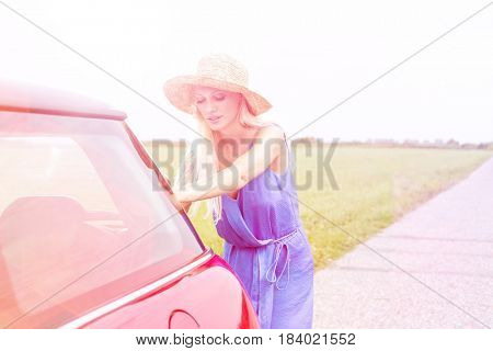 Woman pushing broken down car on country road against clear sky