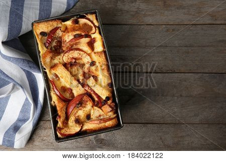 Freshly baked bread pudding in casserole dish on wooden table