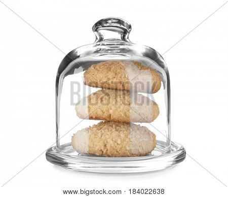 Glass cover with delicious coconut cookies on white background