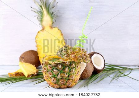 Cocktail in pineapple and coconut on wooden table