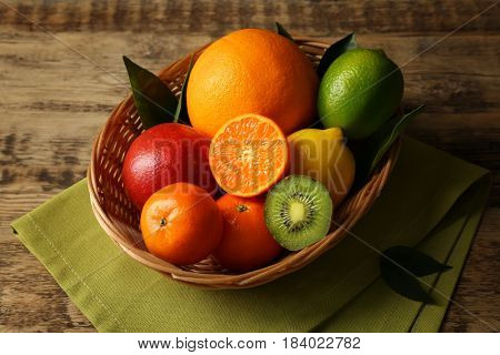 Decorative wicker basket with fresh citrus fruits on wooden background