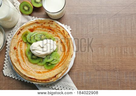 Delicious pancakes with kiwi and sour cream on plate