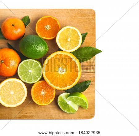 Wooden board with delicious citrus fruits on white background