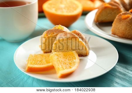 Plate with slices of citrus cake and fresh orange on blue wooden table