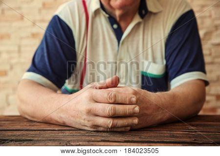 Senior man sitting at table, closeup. Poverty concept