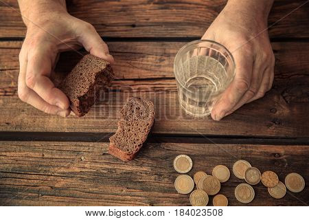Senior man's hands with glass of water, bread and coins on wooden background. Poverty concept