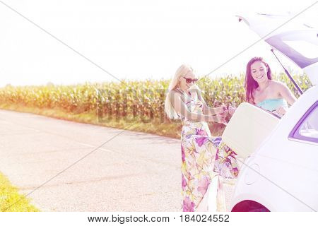 Happy women loading luggage in car trunk against clear sky
