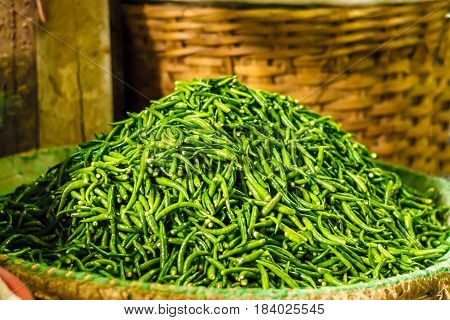 Pile of fresh green chilli peppers in the basket. Raw food. Close up. Traditional vegetable market in Bangkok, Thailand. Sunny day