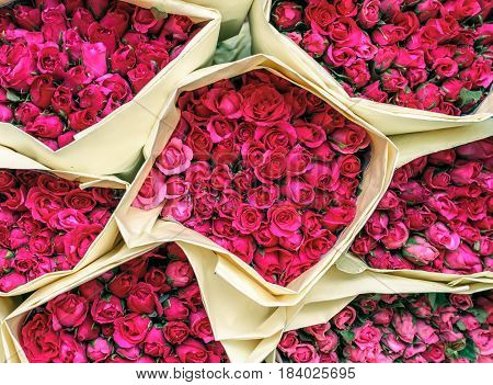 Beautiful pink small roses in paper bouquets, top view, at Bangkok flower market Thailand.
