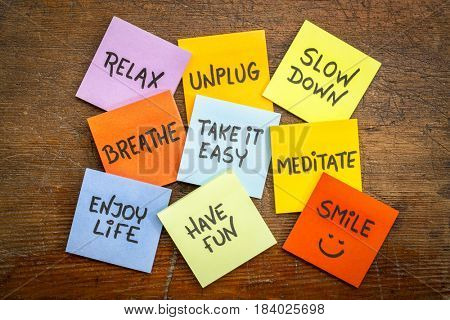relax, unplug, slow down, breathe, take it easy, meditate,enjoy life, have and smile motivational lifestyle reminders on colorful sticky notes against grunge wood
