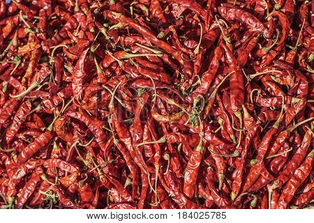Pile of dried red chilli peppers texture. Close up. Traditional vegetable market in Bangkok, Thailand. Selective focus