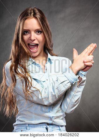 Woman Having Fun Pretending Hand Finger Is A Gun.