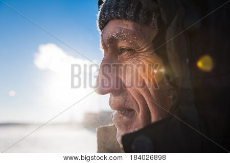Man with a beard wearing a cap with a ushanka polar explorer a manly strong brutal on the background mountain nature Svalbard Longyearbyen Svalbard Norway with blue sky and snowy peaks wallpaper.