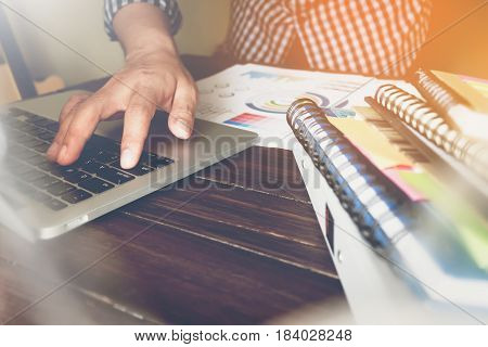 businessman hand working laptop on wooden desk Use the accompany article in finance. vintage effect