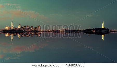 New York City at night with urban architectures reflections and statue of liberty