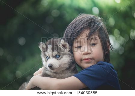 Sad asian child hugging siberian husky puppy