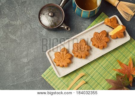 Japanese food traditional maple leaf cake dessert and green tea on dark background. View from above