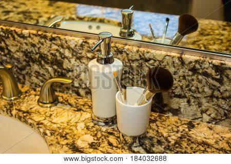 Lotion Dispenser & Makeup Brushes In Bathroom