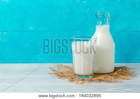 Milk bottle and glass on wooden table over blue background with copy space. Jewish holiday Shavuot concept