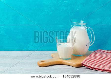 Milk on wooden table over blue background with copy space. Jewish holiday Shavuot concept