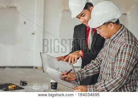 Management Consulting With Engineers Working With Blueprint And Drawing On Work Table In For Managem