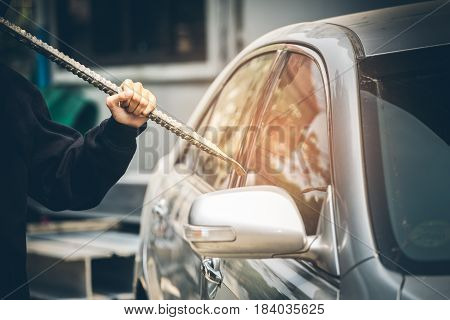 A Robber Dressed In Black Holding Crowbar At A Driver In A Car. Car Thief Concept.