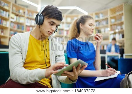 Serious student with headphones and touchpad watching video at break