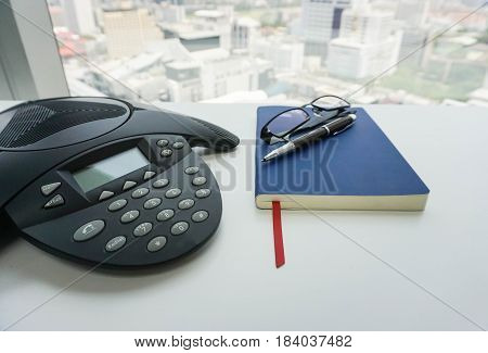 close up voip IP conference phone with notebook and eyeglasses for meeting in office